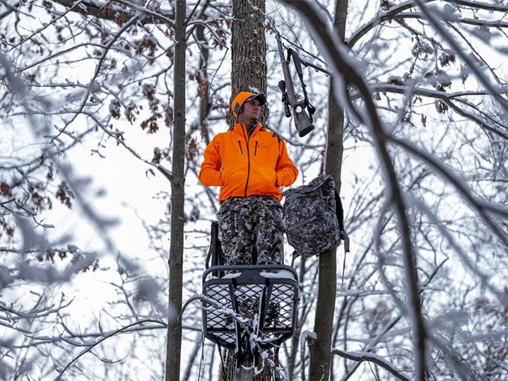 Stratus Jacket in Blaze Orange rifle hunting from a tree stand